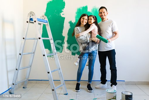 istock Portrait of a good-looking mom, dad and daughter painting the house 1297875455
