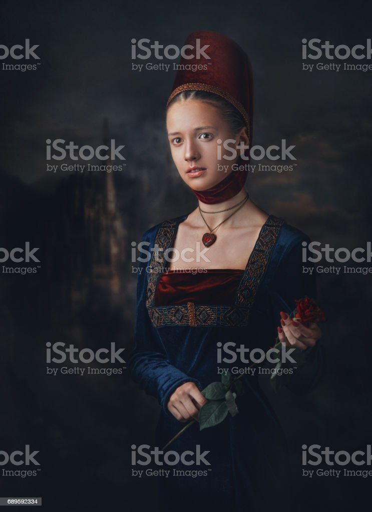 Portrait of a gorgeous girl in medieval era dress and headdress. Medallion in a shape of heart. Holding red rose in hands. stock photo