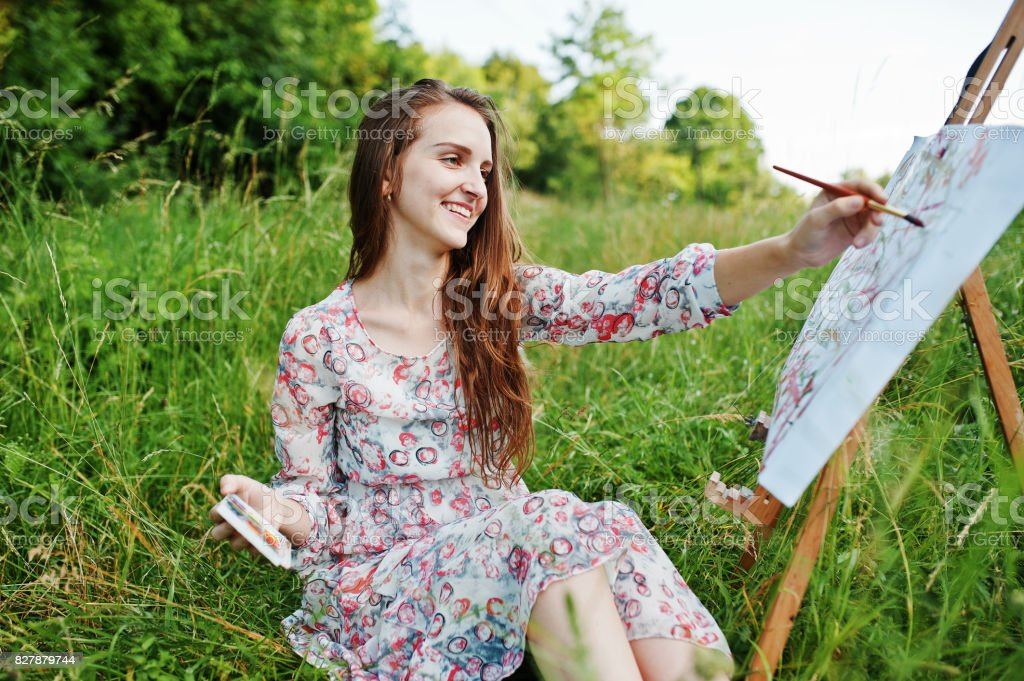 4d43b350bf Portrait of a gorgeous happy young woman in beautiful dress sitting on the  grass and painting on paper with watercolors. - Stock image .
