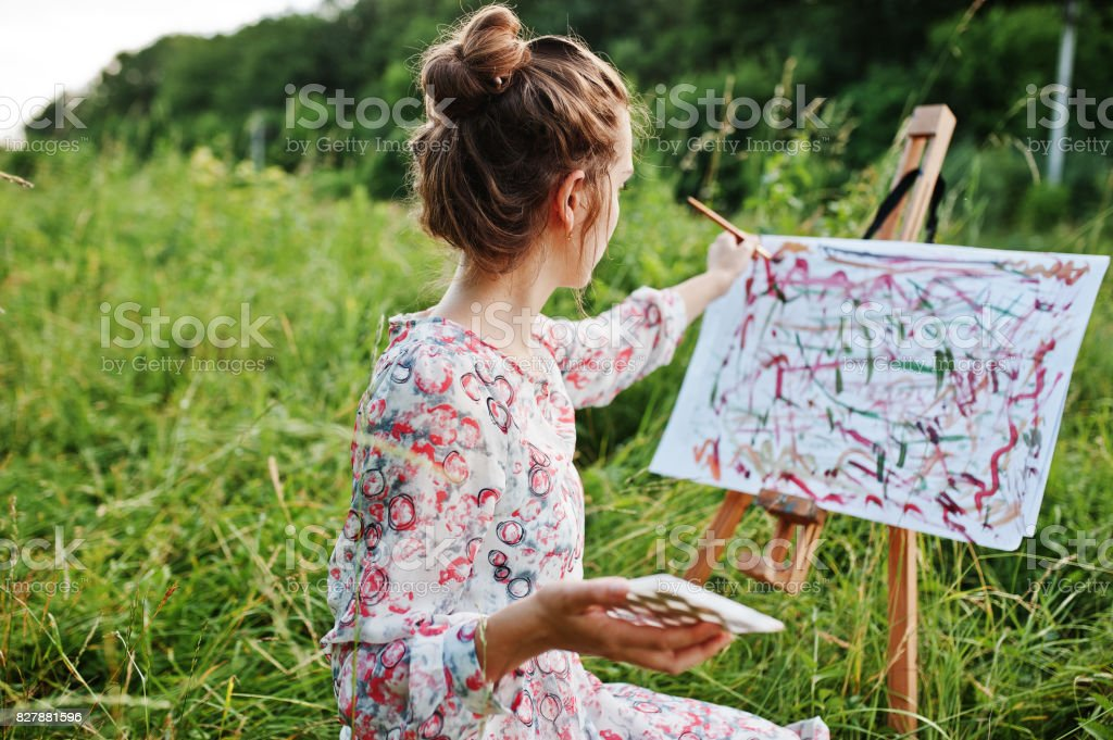 9e423dd749 Portrait of a gorgeous happy young woman in beautiful dress sitting on the  grass and painting