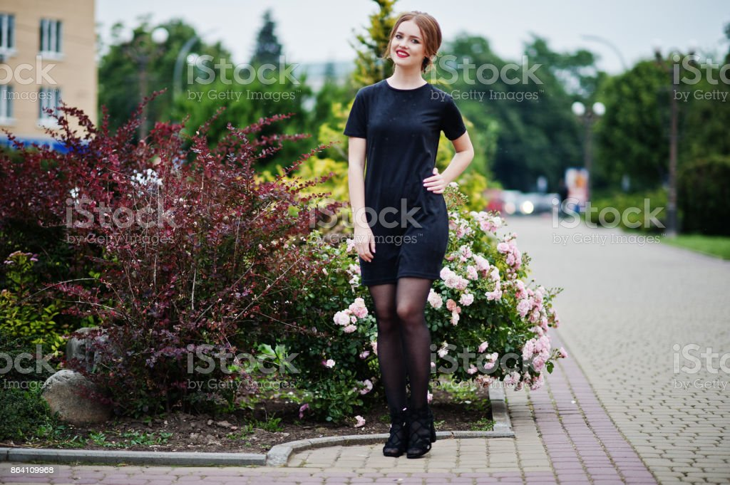 Portrait of a gorgeous young girl in black dress walking on the pavement in the park on a prom day. royalty-free stock photo