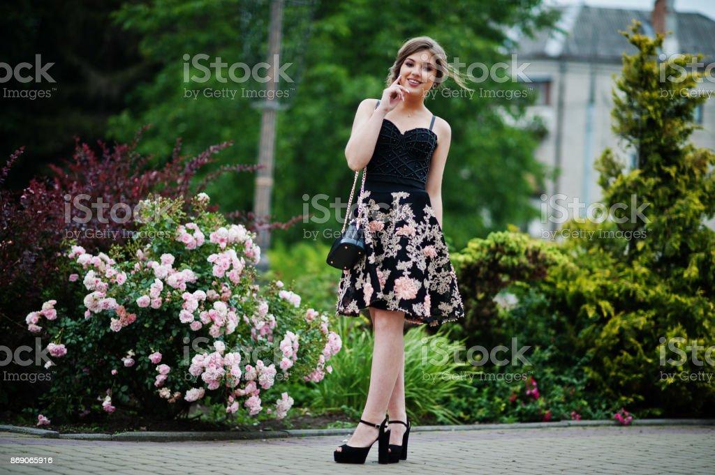 Porträt von einem wunderschönen jungen Mädchen in schwarz geblümten Kleid zu Fuß auf dem Bürgersteig mit Ledertasche im Park auf einem Abschlussball-Tag. – Foto