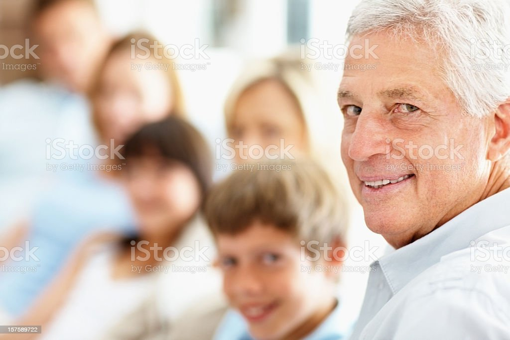 Portrait of a grandfather smiling with family in the background Closeup portrait of a grandfather smiling with family in the background Multi-Generation Family Stock Photo