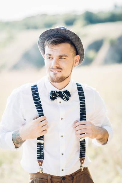 portrait of a groom in  bow tie at the wedding - pantolon askısı stok fotoğraflar ve resimler
