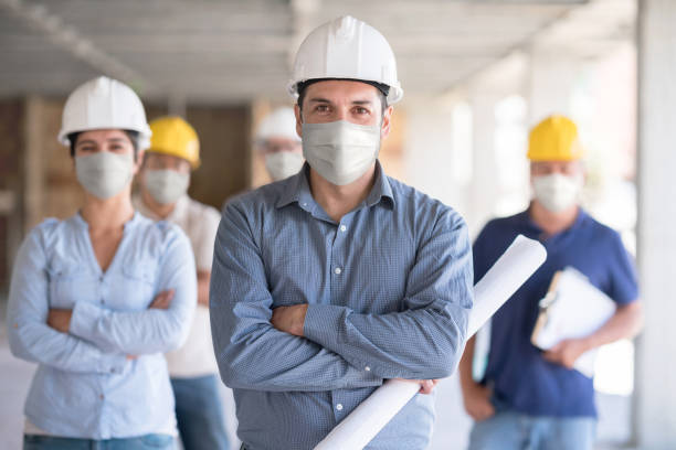 Portrait of a group of engineers wearing facemasks at a construction site stock photo
