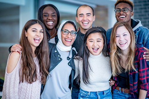 A varying group of young adults stand and smile with their arms around each other. They could be university or college students.
