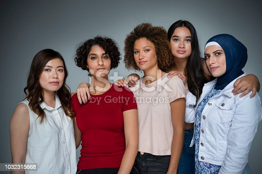 Portrait of a Group of women in the studio. Multi-ethnic group including Caucasian, Hispanic, middle eastern, Asian and African American. One middle eastern woman is wearing a hijab