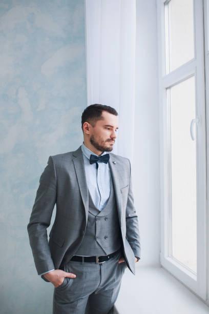porträt von einem erwachsenen mann einen grauen anzug im studio. der bräutigam wartet auf die braut. hochzeit - hochzeitsanzug herren stock-fotos und bilder