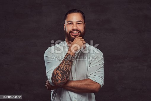 istock Portrait of a handsome African-American tattooed man with stylish hair and beard in a white shirt, holding hand on his chin. 1028400872