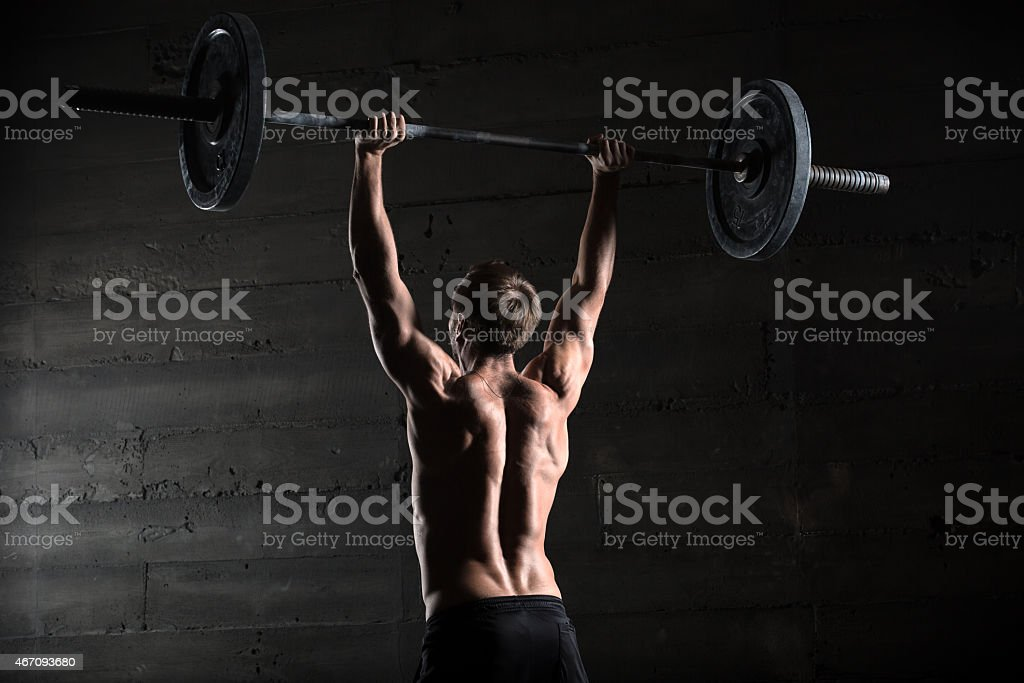 Portrait of a handsome athlete from behind. Athlete raises the stock photo