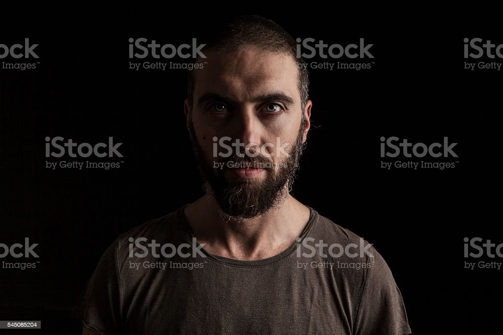 portrait of a handsome bearded man on dark background stock photo