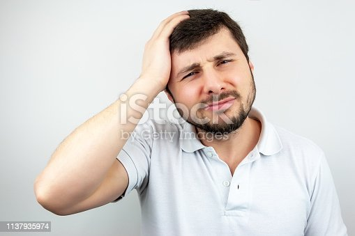 534891769 istock photo Portrait of a handsome bearded man suffering from headache 1137935974