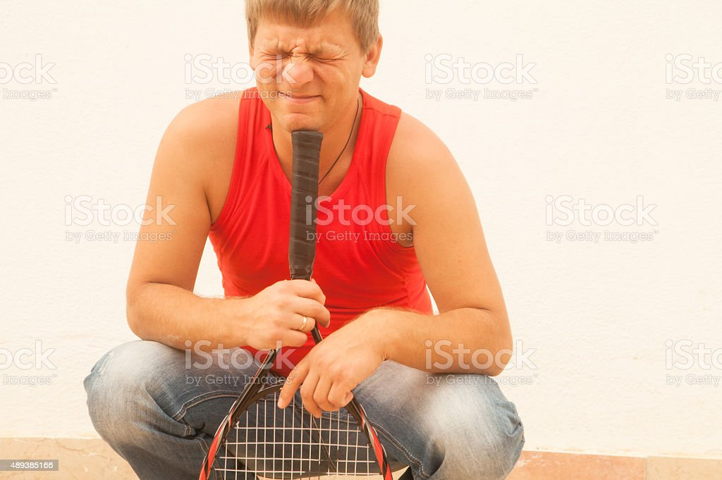 Portrait of a handsome blond man with tennis racket stock photo