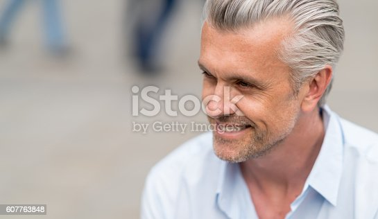 Portrait of a handsome business man smiling outdoors - lifestyle concepts