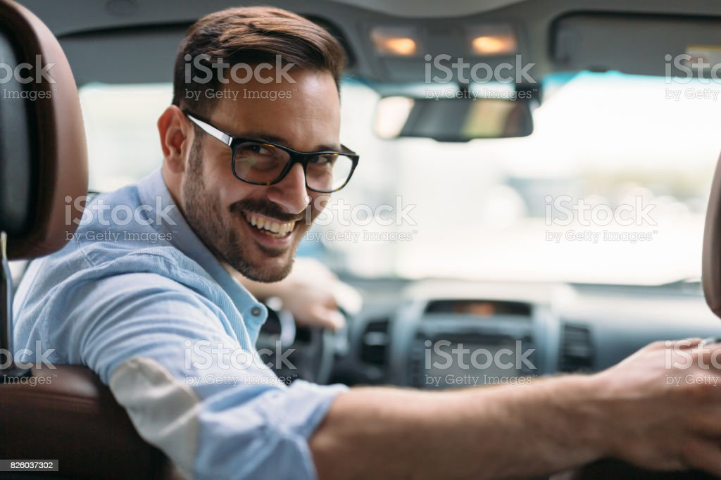 Portrait of a handsome businessman driving car stock photo
