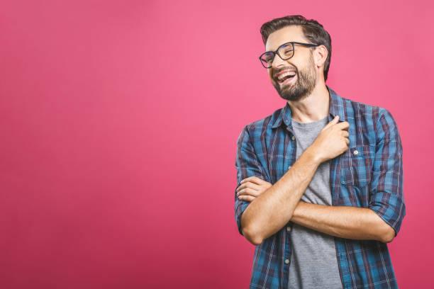 porträt eines hübschen gelegenheitsmannes, der lacht, steht und über rosa hintergrund lacht - junger mann stock-fotos und bilder