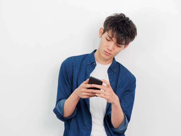 Portrait of a handsome Chinese young man in blue shirt looking at her mobile phone, serious or worried expression, isolated on white background. stock photo