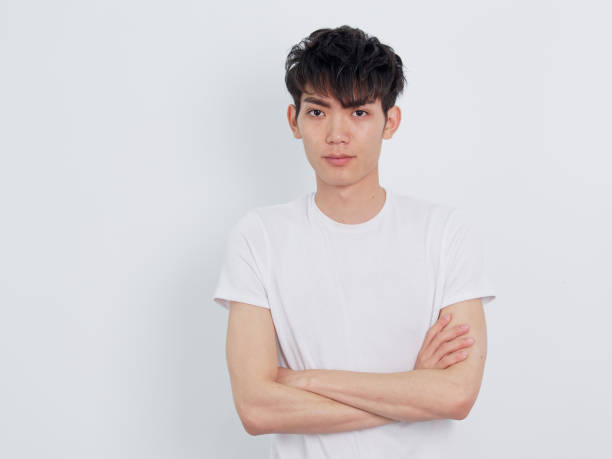 Portrait of a handsome Chinese young man in blue shirt looking at camera with two arms crossed, confident expression, isolated on white background. stock photo