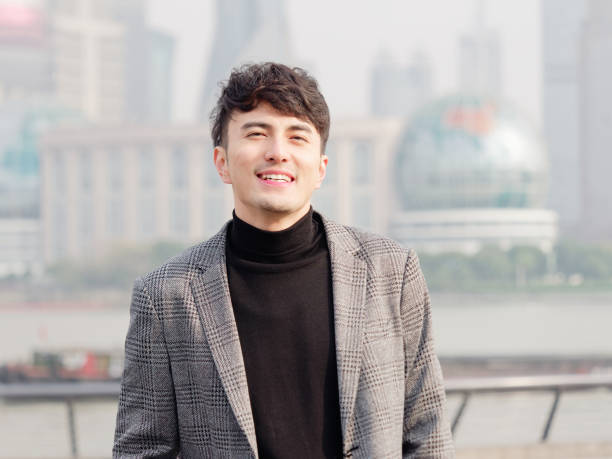 Portrait of a handsome Chinese young man in casual suit smiling and looking at camera confidently with Shanghai bund background, winter fashion, cool young man lifestyle. Portrait of a handsome Chinese young man in casual suit smiling and looking at camera confidently with Shanghai bund background, winter fashion, cool young man lifestyle. huangpu district stock pictures, royalty-free photos & images
