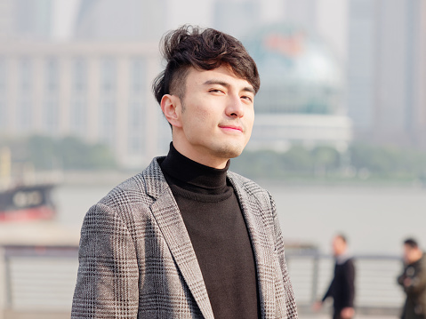 Portrait Of A Handsome Chinese Young Man In Casual Suit Smiling And Looking  At Camera Confidently With Shanghai Bund Background Winter Fashion Cool  Young Man Lifestyle Stock Photo - Download Image Now -