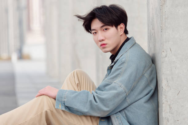 Portrait of a handsome Chinese young man in jeans sitting on ground and looking at camera. stock photo