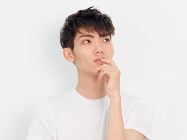 Portrait of a handsome Chinese young man in white t shirt looking away with hand on his lips, thinking expression, isolated on white background. stock photo