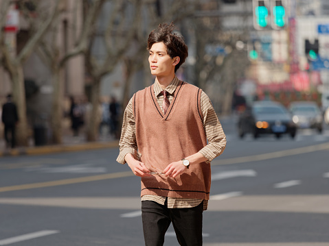 Portrait of a handsome Chinese young man with Korean style clothes walking on street in hurry in sunny day, male fashion, cool Asian young man lifestyle.