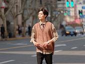 晴れた日、男性のファッション、クールなアジアの若い男のライフスタイルで急いで通りを歩いている韓国のスタイルの服を持つハンサムな中国の若い男の肖像画。