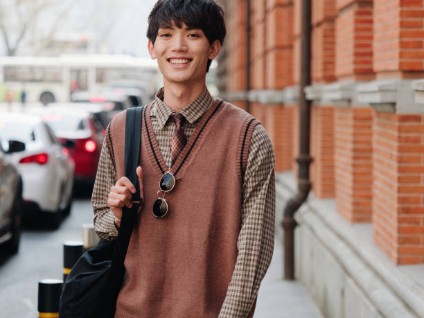 Portrait of a handsome Chinese young man with Korean style clothes smiling and looking at camera confidently with street background, male fashion, cool Asian young man lifestyle stock photo