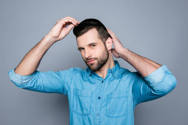 a portrait of a handsome confident man in jeans shirt combing his hair - take care of your jeans imagens e fotografias de stock