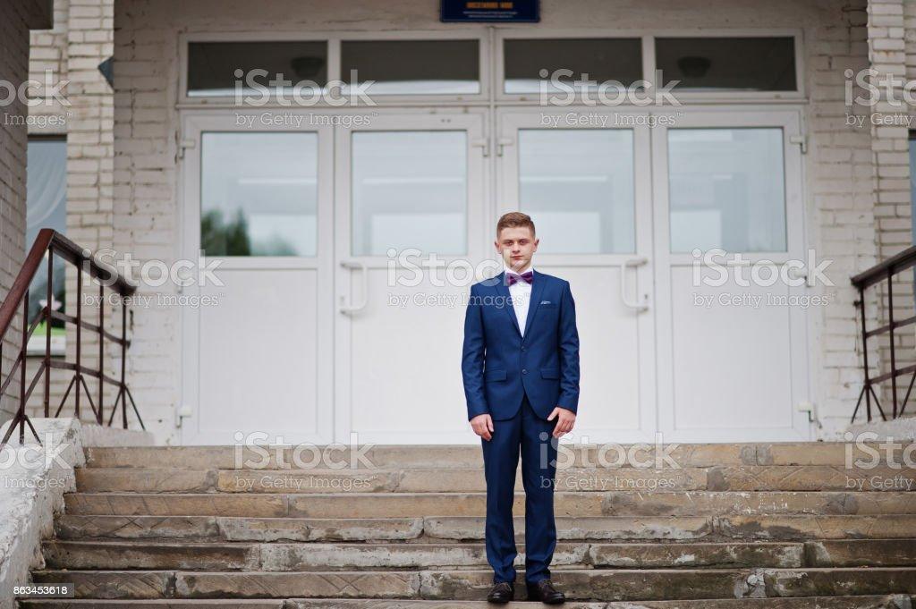 Porträt von ein schöner High School Diplom im eleganten Smoking posiert auf der Treppe auf den Abschlussball. – Foto
