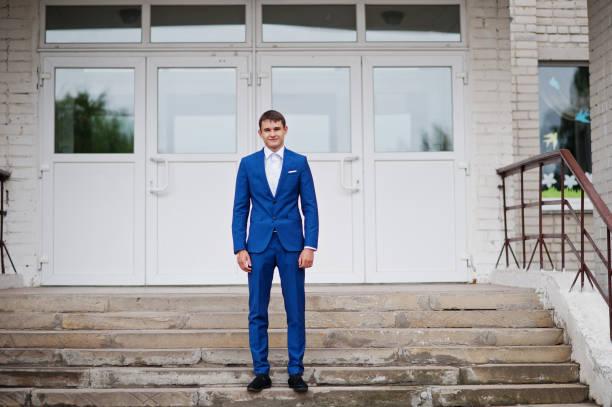 porträt von ein schöner high school diplom im eleganten smoking posiert auf der treppe auf den abschlussball. - high school abschlußball stock-fotos und bilder