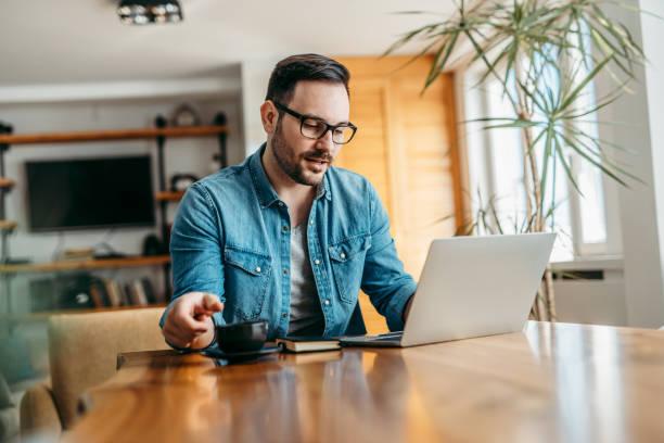 Retrato de un hombre guapo teniendo videollamada en la computadora portátil y bebiendo una taza de café. - foto de stock