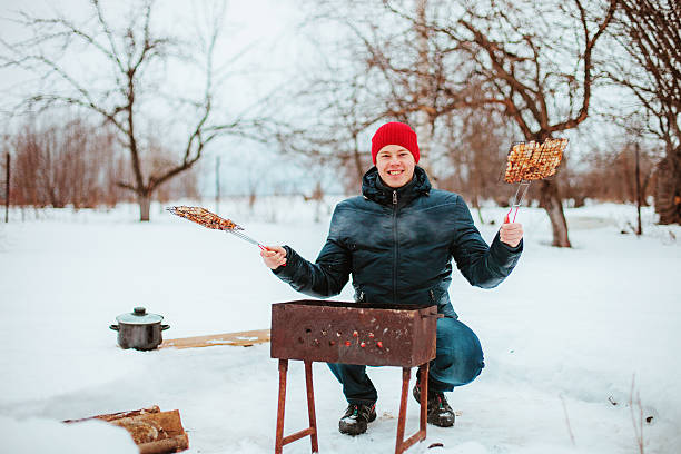 A portrait of a handsome man holding a barbecue in the snow stock photo