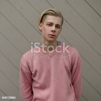846124694 istock photo Portrait of a handsome man in a pink sweater near a wooden wall 846126964