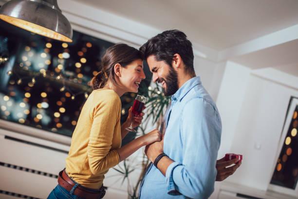 ボックスに婚約指輪を押しながら幸せな恋人に提案しハンサムな男の肖像 - ボーイフレンド ストックフォトと画像