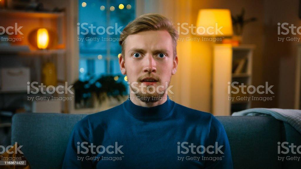 Porträt eines hübschen Mannes, der nachts zu Hause auf einer Couch sitzt und Gore Horror Film im Fernsehen sieht. Er bekommt wirklich Angst, verwirrt und empört. - Lizenzfrei Abenddämmerung Stock-Foto