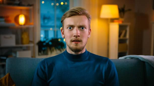 porträt eines hübschen mannes, der nachts zu hause auf einer couch sitzt und gore horror film im fernsehen sieht. er bekommt wirklich angst, verwirrt und empört. - film oder fernsehvorführung stock-fotos und bilder