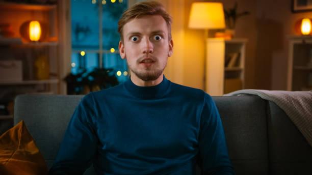 portret van een knappe man zittend op een bank thuis 's nachts, kijken vermakelijke film op tv. hij is echt geest geblazen en geschokt door enorme verkoop en kortingen toonde in reclame. - amfetamine stockfoto's en -beelden