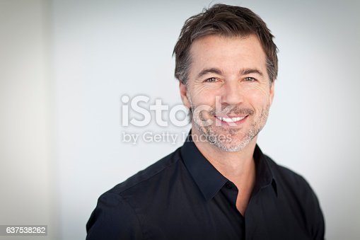 istock Portrait Of A Handsome Man Smiling Isolated On White 637538262