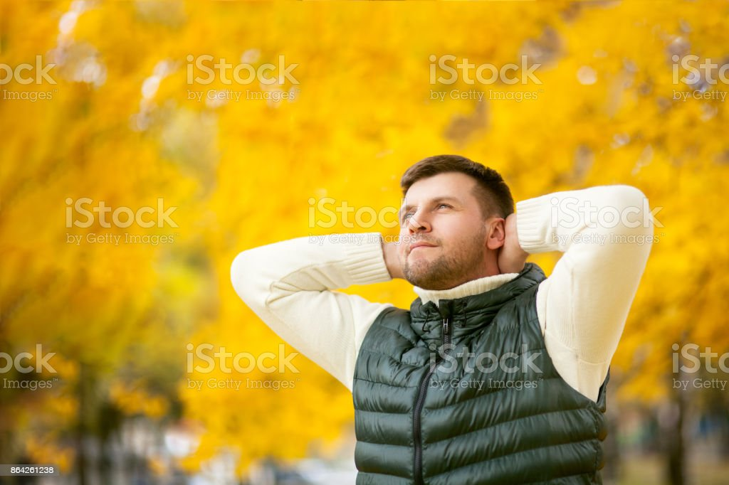 portrait of a handsome man with hands behind his head in an autumn park royalty-free stock photo