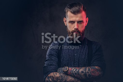 istock Portrait of a handsome old-fashioned hipster in a blue shirt and suspenders, standing with crossed arms in a studio. 1018773252
