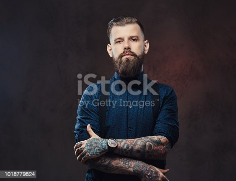 istock Portrait of a handsome old-fashioned hipster in a blue shirt and suspenders, standing with crossed arms in a studio. 1018779824