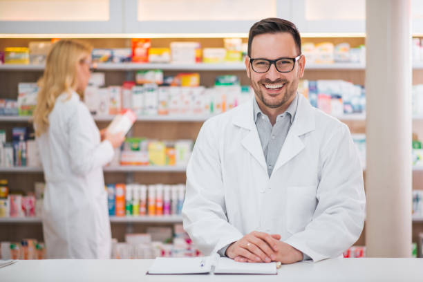 Portrait of a handsome pharmacist at the counter of a drugstore, female colleague working in the background. stock photo