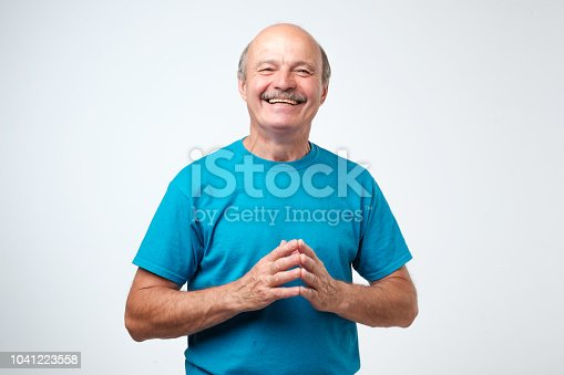 Portrait of a handsome senior hispanic man in blue t-shirt laughing