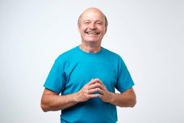 porträt eines schönen senior im blauen t-shirt lachen - einzelner senior stock-fotos und bilder