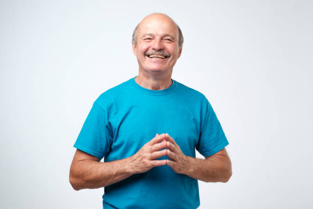 Portrait of a handsome senior man in blue t-shirt laughing Portrait of a handsome senior hispanic man in blue t-shirt laughing only senior men stock pictures, royalty-free photos & images