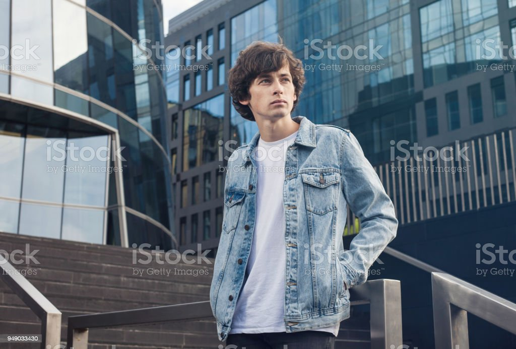 395b38a7 Portrait of a handsome thoughtful young man wearing jeans jacket standing  on stairs against city background - Stock image .