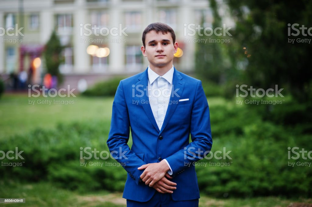 Porträt von einem schönen jungen Mann gekleidet in coolen Anzug posiert auf dem Rasen auf seinem Abschlussball-Tag. – Foto