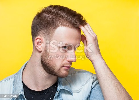 932956896istockphoto Portrait of a handsome young man in a barber shop on a yellow background. 941872440